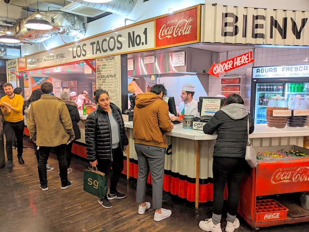 Hungry patrons waiting for their tacos at Los Tacos No. 1 in NYC.
