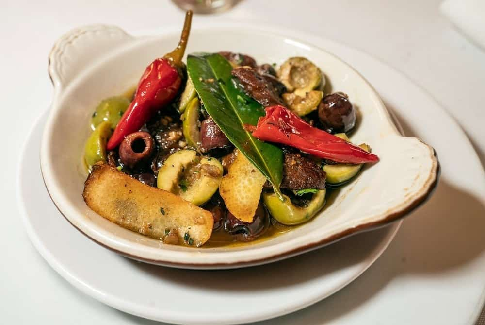 Sautéed vegetables in a plain white dish from Nice Matin, one of the best thing to do in the Upper West Side NYC.