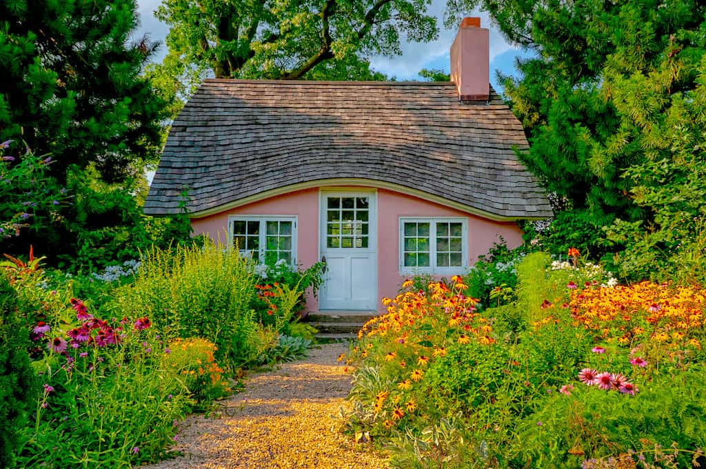 The pink playhouse surrounded by flowers at Planting Fields Arboretum.