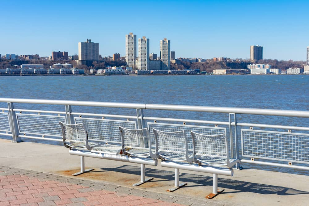 An empty metal bench at Pier I facing the Hudson River in Lincoln Square of New York City with a clear blue sky