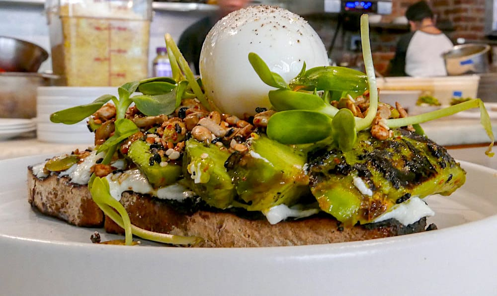 Avocado toast from Sunday in Brooklyn with whipped ricotta, sprouts, toasted seeds, and a six-minute egg on top.