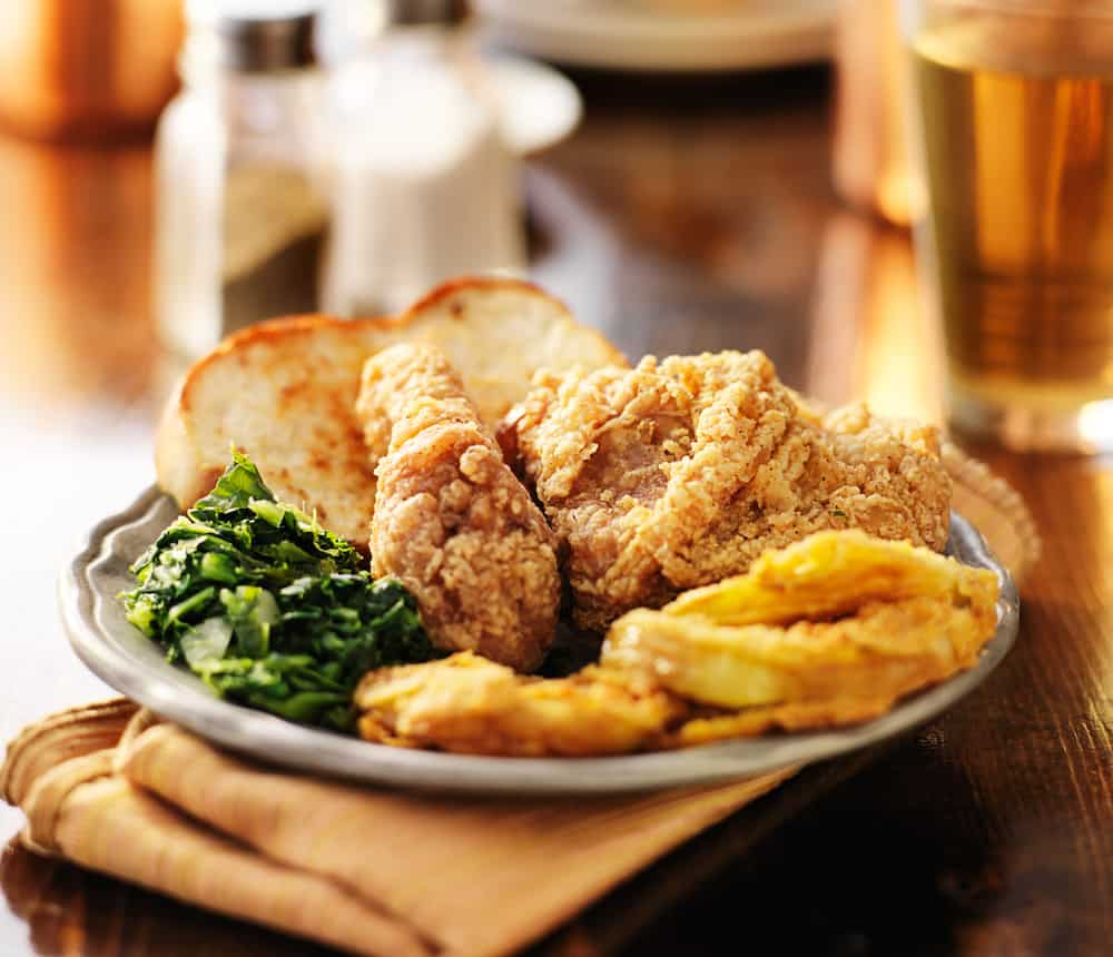 A plate of Southern fried chicken with collard greens on a wooden table.