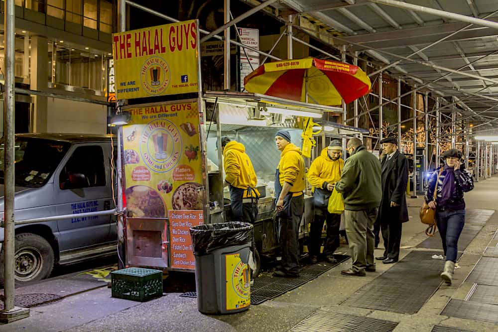 The Halal Guys, a street vendor is seen selling Halal food in Manhattan as a woman walk by talking on her cell phone.