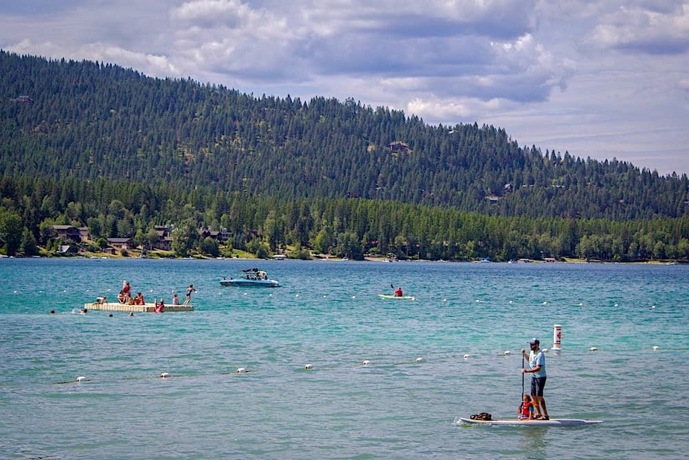 People swimming, kayaking, and paddle boarding in Whitefish Lake in Montana.