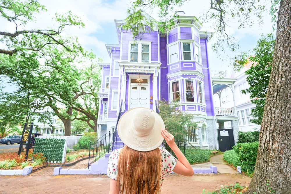 Woman in a hat standing in front of a purple house in Savannah, Georgia.
