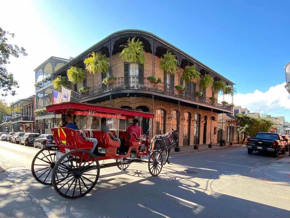 Horse drawn carriage going through the French Quarter in New Orleans, one of the best warm places to visit in December.