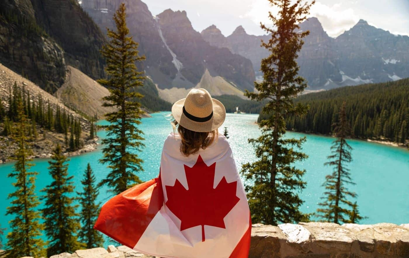 Woman draped in a Canadian flag looking out at a beautiful lake.